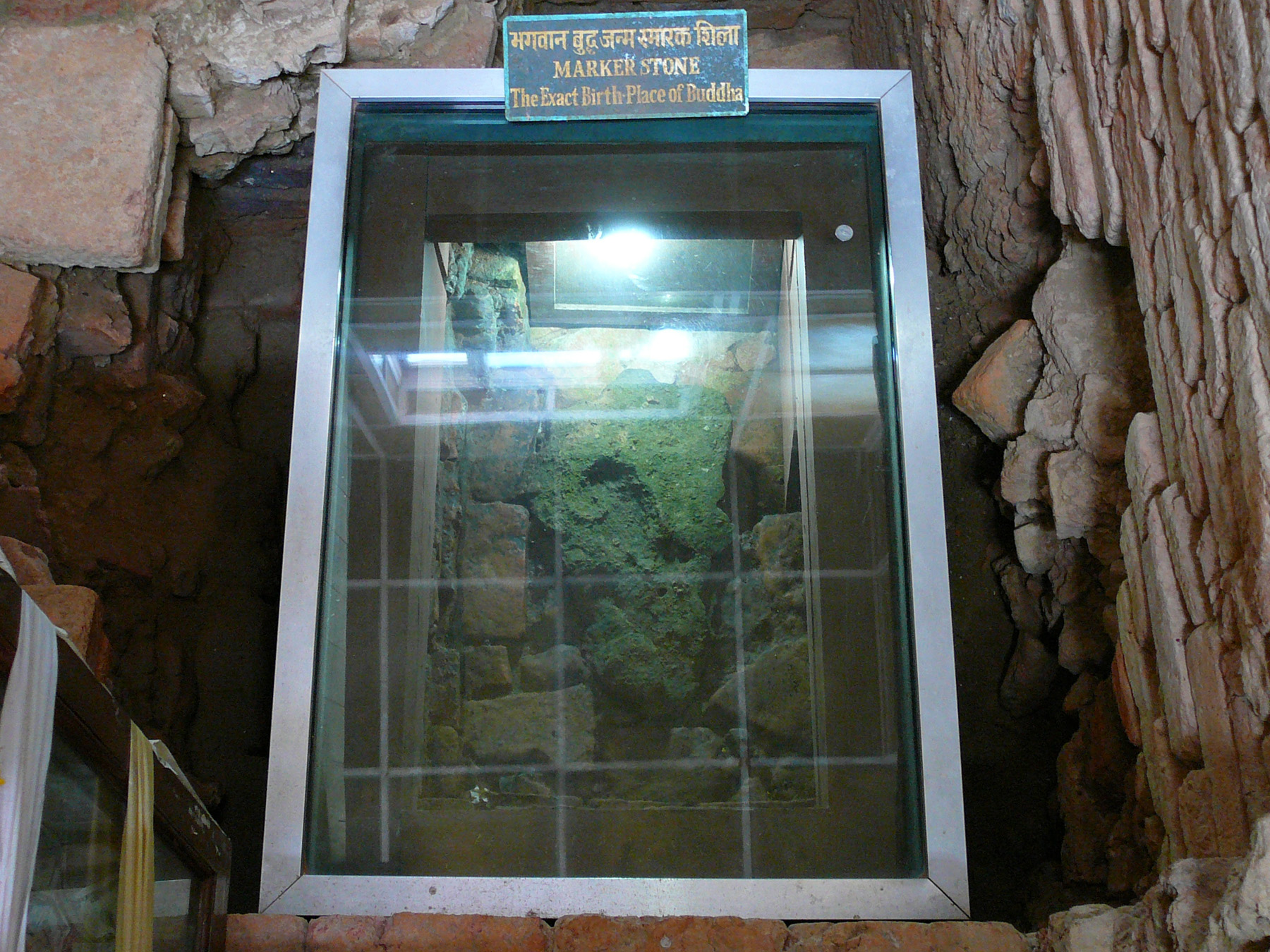 Phiến đá có in dấu một bàn chân nhỏ, mà vua A Dục vào năm 249 TCN đã dùng để đánh dấu vị trí nơi sinh của đức Phật. Phiến đá được bảo vệ bằng kính chống đạn tại đúng vị trí được tìm thấy. | Marker stone marking the exact spot of Lord Buddha's birth inside Mayadevi Temple, Lumbini